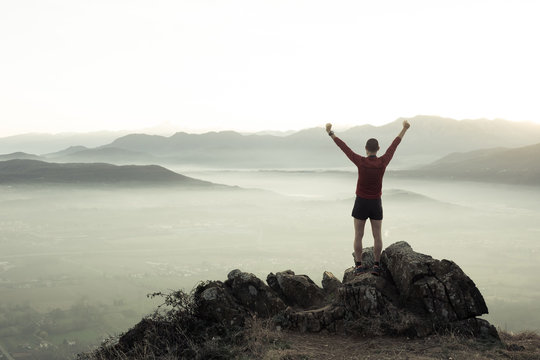 Man at the top of a mountain looking the landscape