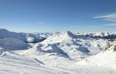 Winter Alpine mountains panorama snow slope with skiing and snowboarding people