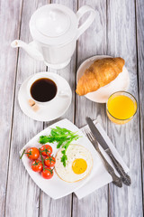 Breakfast with cup of coffee, egg, croissant and orange juice on wooden table