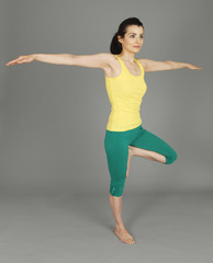 A young woman standing on one leg arms outstretched.