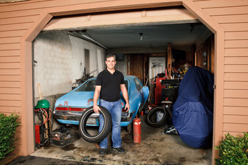 Middle-aged man standing in cluttered garage holding a tire