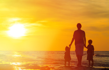 father and kids walking on beach at sunset