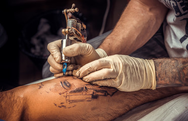 Professional tattooist makes tattoo pictures in tattoo studio