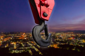 Close up of heavy-duty steel hook on night city scape