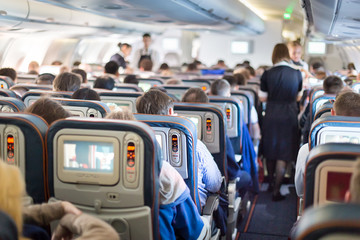 Interior of airplane with passengers on seats. Wall mural
