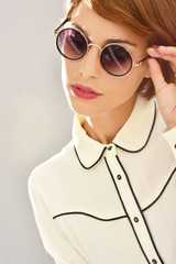 Closeup of trendy young woman with sunglasses on, isolated