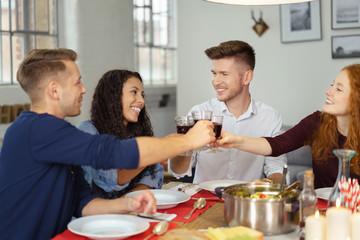 freunde essen zusammen und stoßen mit rotwein an