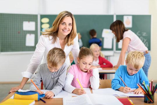 freundliche lehrerin mit kindern in der grundschule
