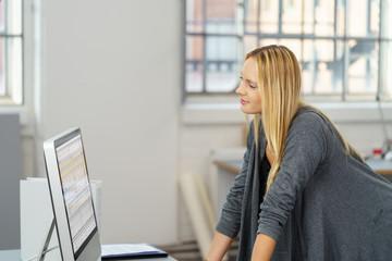 frau im büro schaut zufrieden auf die zahlen im computer