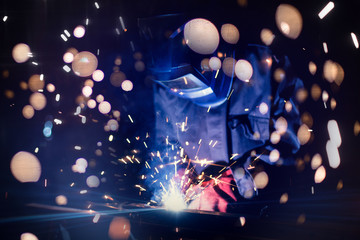 Employee welding steel with sparks using mig mag welder - focus on sparks.