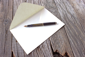 Fountain pen and letter on wooden background