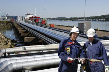 fuel pipelines leading to ships with two refinery workers in foreground