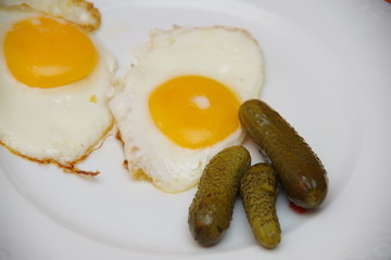 eggs, and pickles on a white plate