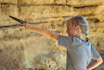 Little girl with old musket gun aiming.