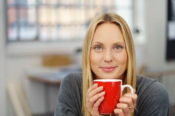lächelnde junge frau mit einer tasse tee
