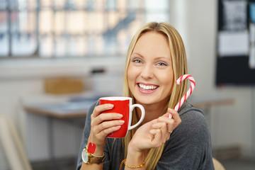 lachende frau im büro mit einer tasse tee und zuckerstange