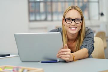 studentin sitzt am schreibtisch und arbeitet am notebook