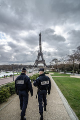 Paris , Paris Security agents guard the Eiffel Tower / Paris, France - March 18, 2012: Patrols of two police officers in the Trocadero gardens and Eiffel Tower.