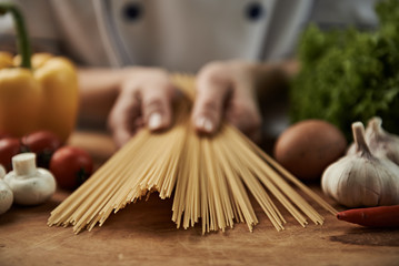 Female chef holding raw spaghetti ready to prepare italian food with vegetables.