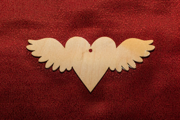 Heart with wings on red fabric background