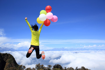 cheering young woman jumping on mountain peak with colorful balloons