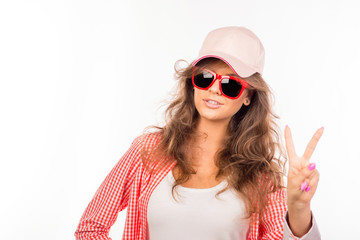 Happy young woman with glasses and hat showing two fingers