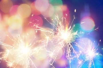 Burning christmas sparkler on colorful light background
