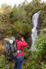 Girl tourist photographing a waterfall. In Portugal, the village Monchique.
