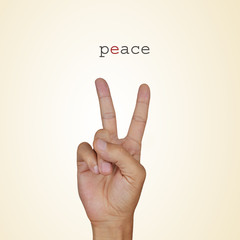 man hand giving the V sign and the word peace