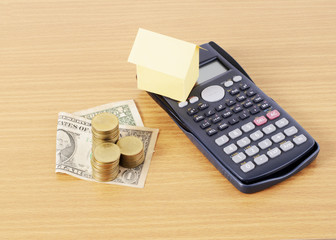 Calculator and home paper and Dollar money with coins stack on Wooden desk for Loans concept