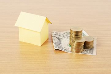 Home loans concept with dollar money and coins stack on wooden desk background