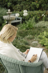 Blond woman sitting in a wicker chair in a garden, writing.