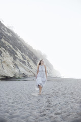Blond woman walking on a sandy beach near a cliff.