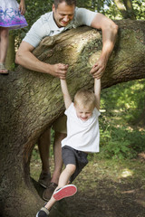 Father playing with his son by a tree in a forest.