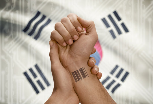 Barcode ID number on wrist of dark skinned person and national flag on background - South Korea