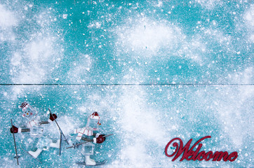 Winter welcome sign with skier on snowy teal blue background
