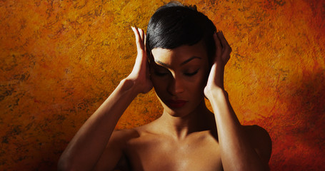 Portrait of nude female model holding her head