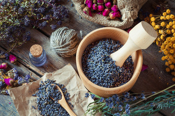 Healing herbs, wooden mortar with lavender, bottles of tincture,