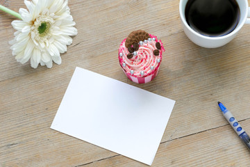 Blank paper with coffee, cupcake and flower on a wooden table, top view.