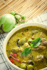 Thai food the pork green curry and eggplant on bamboo background
