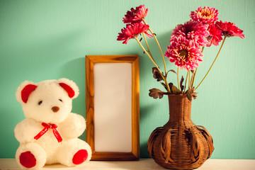 Teddy bear,picture frame,flower in vase on white,green wood back