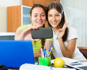 Girls making photo on mobile phone