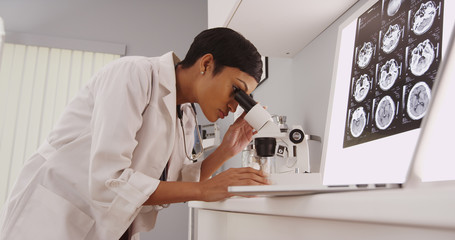 Young intelligent  female doctor looking in a microscope