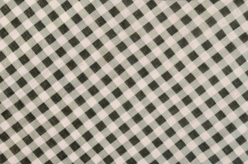Close up on checkered tablecloth fabric. Green and white tartan square pattern as background.