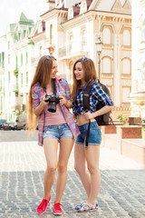 Two pretty young tourists looking at the screen of a camera and