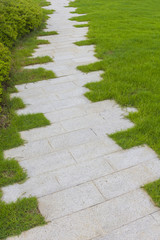 Stone paving footpath on grass field