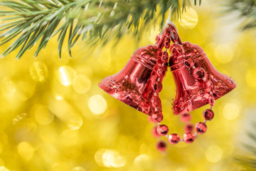 Christmas bell ornament hang on tree branch with yellow bokeh ba