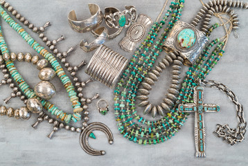 A collection of Vintage Native American Jewelry made of Turquoise and Sterling Silver. Necklaces, cuff bracelets, Squash Blossom and a Silver Cross