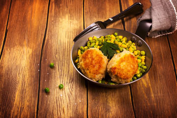 Chicken cutlets with vegetable garniture in metal skillet over wooden background, top view