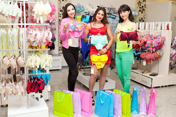 Three beautiful girls in the store to buy underwear
